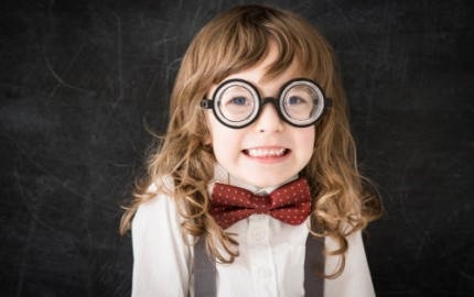 Curly-headed mischief nerd kid in class. Funny geek against blackboard. Education concept